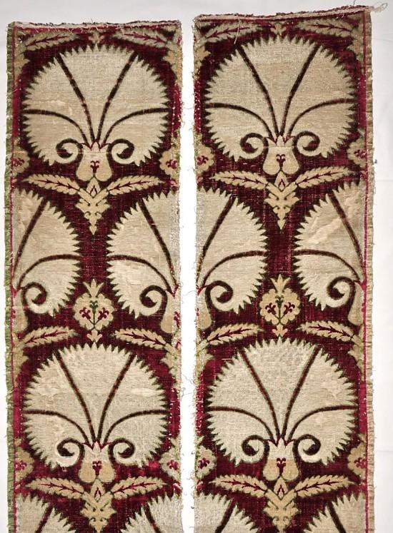 Fragmenty pasa kapy z widocznymi brzegami warsztatowymi w kolorze kremowym i zielonym (szer. 1cm); w górnej części obu fragmentów zachowała się krajka pozioma z zakończenia kuponu tkaniny.