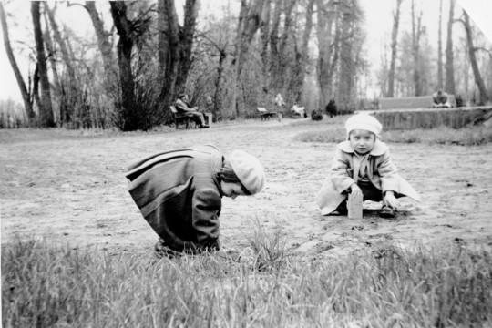 Park, ujęcie z poziomu dziecka. Dwoje dzieci kuca na trawie. Ubrane w berety i płaszczyki. W tle ludzie siedzą na ławkach albo spacerują.