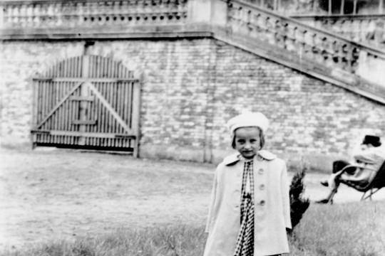 Dziewczynka w płaszczyku i berecie pozuje. Jedną nogę wystawia do przodu.  Ubrana jest w beret, płaszczyk i sukienkę w kratkę.