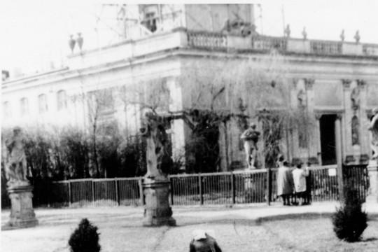 Dziewczynka w płaszczu stoi z rowerem. Jedną nogę opiera na pedale, drugą na ziemi. W tle pałac i ogrodowe rzeźby.