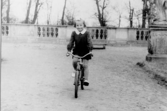 Dziedziniec pałacu. Uśmiechnięta dziewczynka jedzie rowerem.