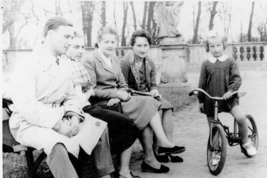 Zbliżenie na mężczyznę i trzy kobiety siedzące na ławce. Rozmawiają. Obok nich stoi dziewczynka z rowerem. Z niezadowoloną miną przygląda się czemuś po prawej stronie.PRWW_DESPERAT_0012_A.jpg