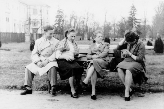 Cztery osoby siedzą na ławce. Mężczyzna uśmiecha się. Kobieta obok niego spogląda na swoje nogi. Druga kobieta siedzi z założonymi nogami i patrzy na czwartą, która przykłada rękę do głowy.