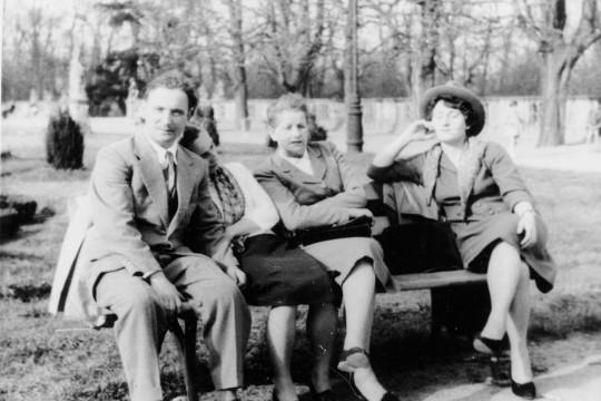 Cztery osoby siedzą na ławce Mężczyzna w garniturze patrzy w obiektyw. Kobieta obok niego opiera głowę na jego ramieniu . druga również spogląda w obiektyw. Trzecia kobieta w kapeluszu wystawia twarz do słońca.
