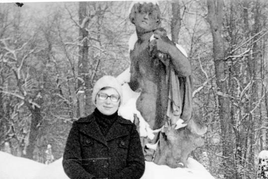 Kobieta w długim płaszczu i okularach pozuje obok rzeźby nagiego mężczyzny. Przed nią zaspa śniegu.