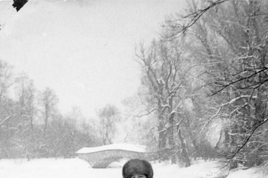 Kobieta w długim kożuchu i puchatej czapce stoi po kolona w śniegu. W tle widać most rzymski i mężczyznę idącego po zamarzniętym jeziorze.