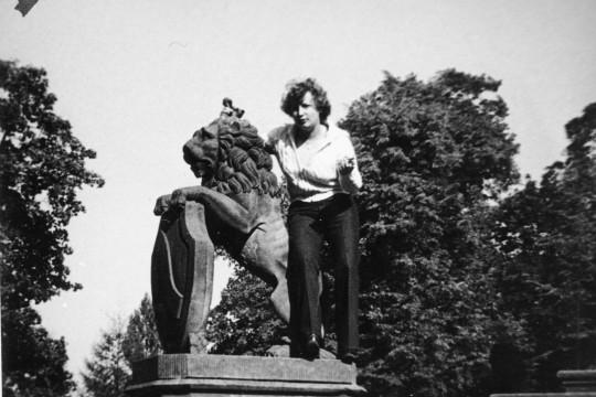 Rzeźba lwa. Zwierzę stoi na tylnych łapach, przednimi wspiera się na tarczy herbowej. Kobieta stoi na podeście rzeźby, lekko ugina nogi udając, że siada na grzbiecie lwa.