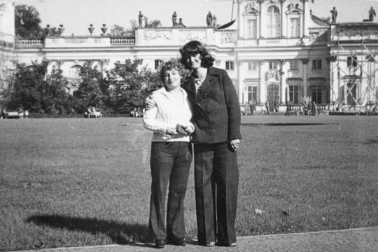 Dwie kobiety na dziedzińcu pałacu. Brunetka obejmuję blondynkę ręką. Uśmiechają się.