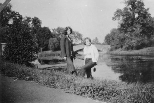Dwie kobiety stoją nad brzegiem Jeziora Wilanowskiego. Patrzą w prawą stronę. Za nimi Most Rzymski.