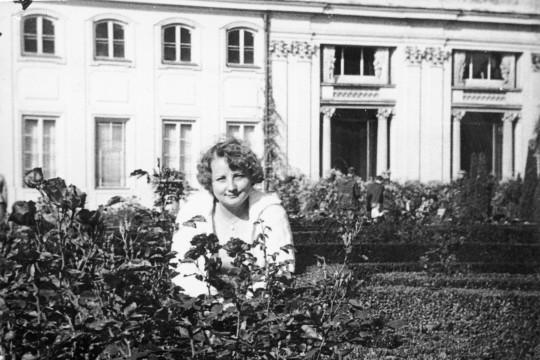 Kobieta pozuje za krzewami róż. Uśmiecha się. Za nią fragment fasady pałacu.