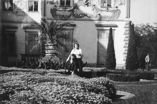 Ogrody przypałacowe. Między rabatkami dwie kobiety. Jedna siedzi. Druga stoi za nią i opiera rękę na jej ramieniu.