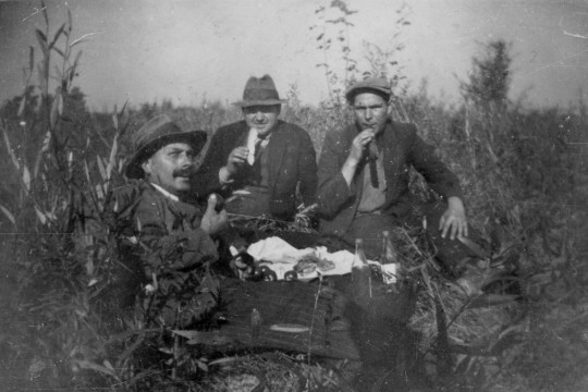 Trzech mężczyzn siedzi w wysokich trawach. Ubrani w garnitury i kapelusze. Jedząm, atmosfera piknikowa.