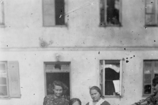 Przed kamienicą siedzi starsza kobieta. Obok niej stoją dwie małe dziewczynki, jedna starsza i jedna dorosła kobieta. Z prawej strony kobieta wyciąga rękę do pozujących, nie widać jej twarzy..