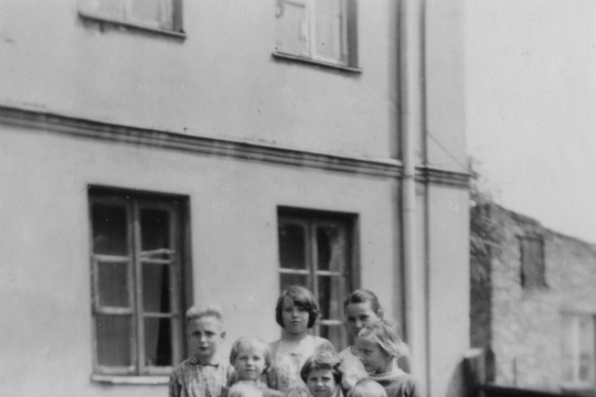 Grupa dzieci w różnym wieku pozuje na podwórku. Stoją wyprostowane i patrzą w obiektyw.