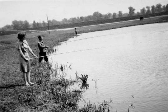 Kobieta i mężczyzna stoją na brzegu jeziora, trzymają wędki, łowią ryby.