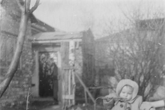 Małe dziecko w zimowym płaszczu. Pcha przed sobą wózek dla lalek. Niewyraźny zarys domu w tle.
