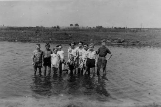 Dziesięcioro dzieci w różnym wieku stoi po kolana w wodzie. Mają na sobie letnie ubrania. W tle pola.