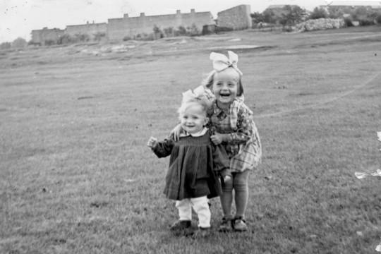 Na pierwszym planie dwoje dzieci. Dziewczynka z kokardą na głowie ugina kolana i przytrzymuje dużo niższe dziecko. Dalej rozległy pas trawy, w tle mury.