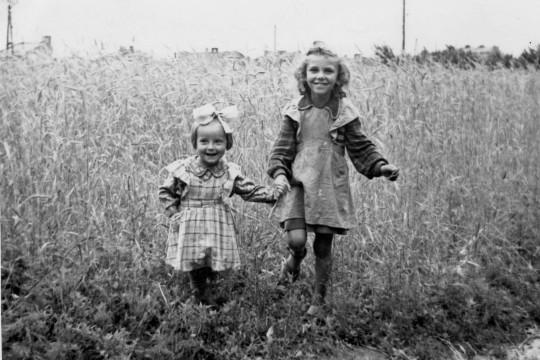 Dwie dziewczynki pozują na tle wysokiego zboża. Obie w sukienkach, jedna ma kokardę na głowie.  Trzymają się za ręce.