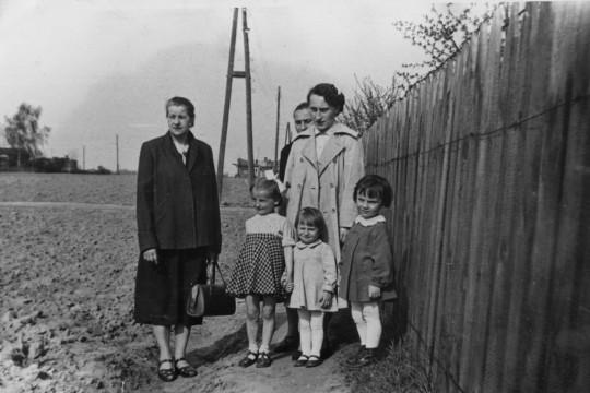 Trzy kobiety i troje dzieci. Elegancko ubrani pozują na polu przy płocie.