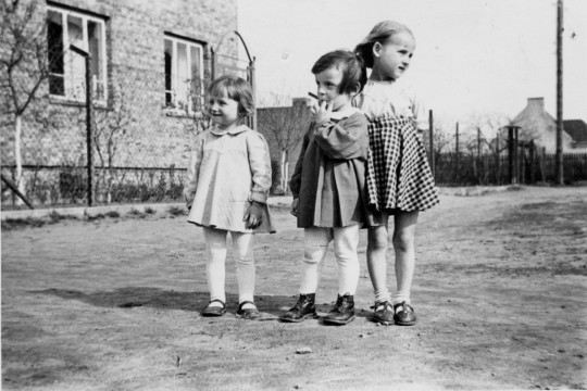 Trzy dziewczynki na drodze. Stoją obok siebie, dwie mniejsze patrzą w prawo, jedna z nich wkłada palec do buzi. Najwyższa  dziewczynka patrzy w przeciwną stronę.