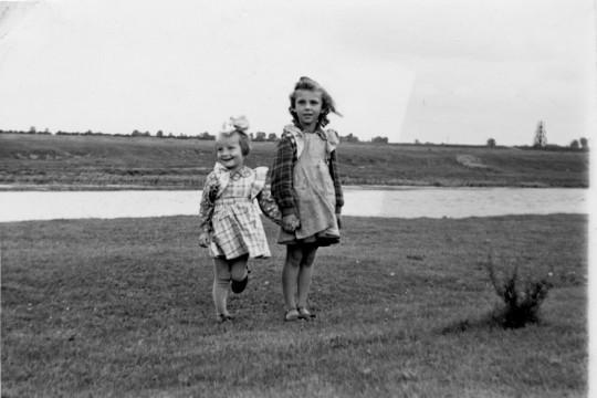 Dwie dziewczynki stoją na trawie. Trzymają się za ręce, uśmiechają. Za nimi rzeka.