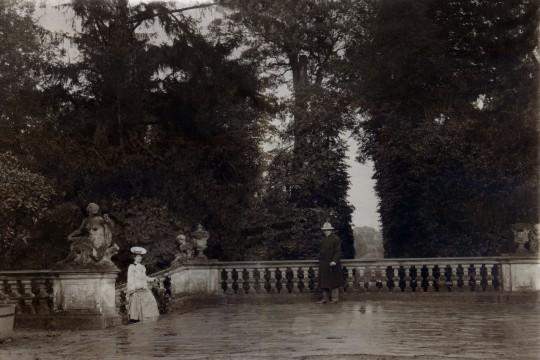 Fotografia w sepii. Taras Górny. Po lewej stronie kobieta w długiej spódnicy i kapeluszu z płaskim rondlem. wchodzi po schodach. Mężczyzna w długim płaszczu opiera się o balustradę.