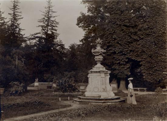 Fotografia w sepii. Ogród z Sarkofagiem Potockiego. Obok niego stoi kobieta, ma na sobie długą spódnicę, koszulę z bufiastymi rękawami i kapelusz.