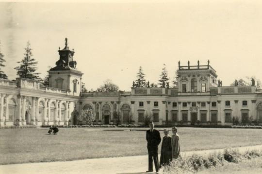 Na ścieżce na dziedzińcu wilanowskiego pałacu pozują mężczyzna i dwie kobiety.