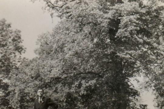 Mężczyzna w garniturze pozuje na wzniesieniu wśród drzew i krzewów. Lewą rękę podpiera na biodrze.