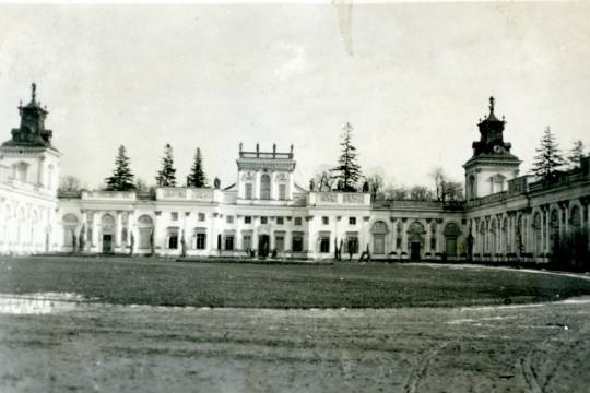 Widok na pałac i dziedziniec. Na dziedzińcu owalny trawnik i błotnista ścieżka dookoła. Przy wejściu do Wielkiej Sieni zarysy postaci.