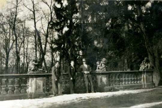 Trzech mężczyzn w garniturach opiera się o balustradę. Na balustradzie w odstępach trzy rzeźby putt.