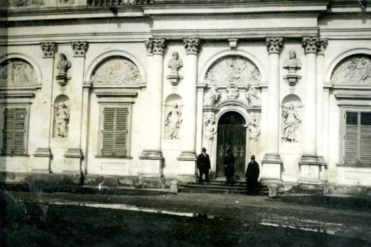 Fasada pałacu. Kolumny i płaskorzeźby. Przy drzwiach stoi trzech mężczyzn w płaszczach.