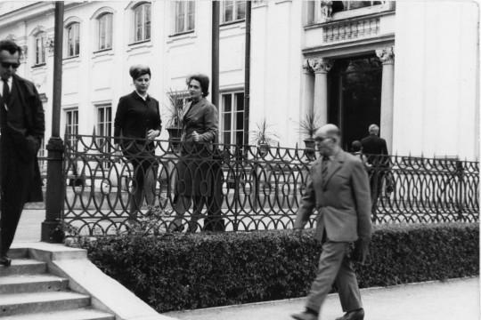 Na pierwszym planie idzie mężczyzna w garniturze. Po lewej stronie schody, po których schodzi inny mężczyzna. Przy balustradzie stoją dwie kobiety. Rozmawiają. W tle fasada budynku.g