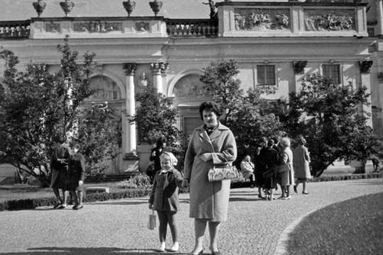 Kobieta trzyma za rękę małą dziewczynkę. Pozują na ścieżce na dziedzińcu na tle pałacu. Kobieta patrzy w obiektyw. Uśmiecha się.