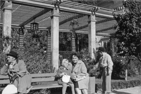 Na ławce siedzi kobieta z dzieckiem, patrzą w obiektyw, obok nich siedzi zamyślony mężczyzna  Z drugiej strony stoi chłopiec. W tle pergola.