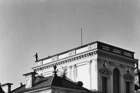 Fragment bogato zdobionej fasady pałacu z perspektywy żabiej. Kobieta stojąca w ogrodzie wydaje się prze to dość mała.