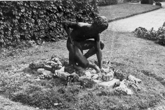 Na kamieniach rzeźba nagiego mężczyzny. Klęczy na jedynym kolanie, jedną rękę kładzie w miejscu, z którego może tryskać woda.