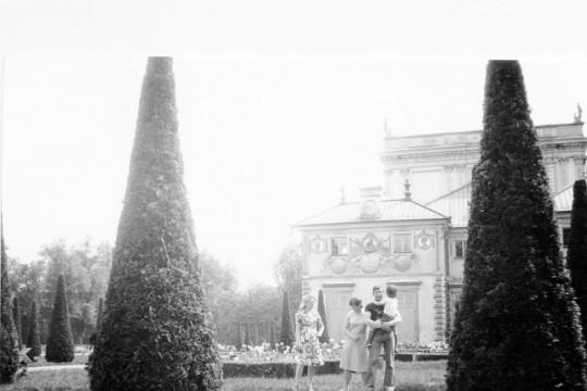 Na pierwszym planie wysokie tuje. Na ścieżce za nimi stoją dwie kobiety i mężczyzna trzymający dziecko. W tle Ogród Różany i fragment pałacu.
