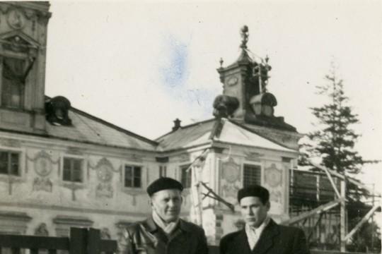 Dwóch mężczyzn stoi na tle remontowanego pałacu. Na ziemi leży śnieg.