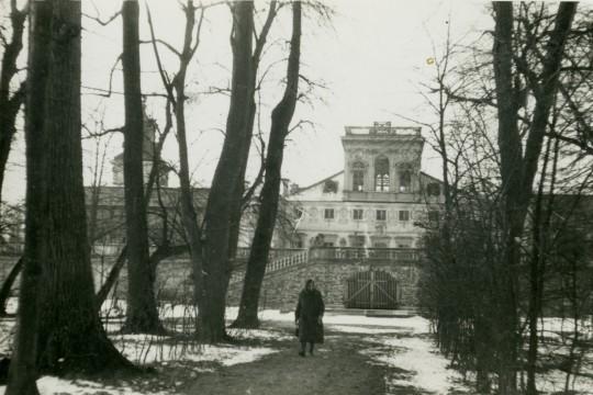 Zima. Kobieta idzie aleją przez park. Za nią widać wejście na taras górny i fragment korpusu głównego pałacu.