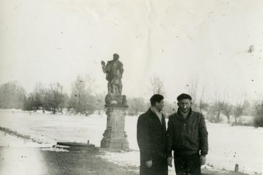 Zima. Dwaj mężczyźni stoją nad ośnieżonym Jeziorem Wilanowskim na tle rzeźby. Jeden z mężczyzn spogląda za siebie.