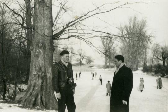 Zima. Na pierwszym planie dwaj mężczyźni, rozmawiają. Za nimi dużo ludzi stoi lub jeździ na łyżwach po zamarzniętym Jeziorze Wilanowskim. W oddali Most Rzymski.