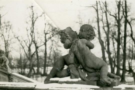 Zbliżenie na rzeźbę na balustradzie Tarasu Górnego. Dwie dziecięce figury puttów w uścisku symbolizujące pocałunek. Na balustradzie śnieg. W tle łyse drzewa.