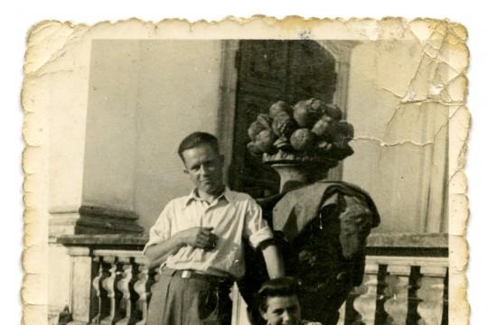 Skan zdjęcia, jasnobrązowe obramowanie z postrzępionymi bokami. Kobieta i mężczyzna przy rzeźbie. Kobieta siedzi na schodach. Mężczyzna stoi obok niej, opierając się o rzeźbę.