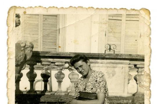 Skan zdjęcia, jasnobrązowe obramowanie z postrzępionymi bokami. Kobieta siedzi na kamieniu. Noga założona na nogę, przytrzymuje torebkę. Lekko pochyla głowę.