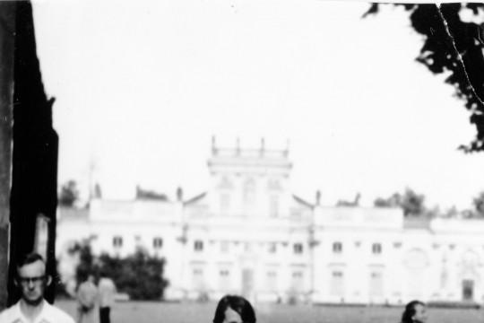 Kobieta w krótkiej białej sukience pozuje. Jedna noga ugięta w kolanie. Obok niej przechodzi mężczyzna. W tle niewyraźny, prześwietlony pałac.