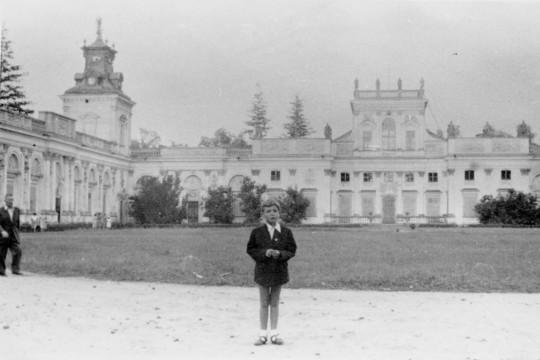 Chłopiec w marynarce i krótkich spodenkach stoi na dziedzińcu. W tle pałac.