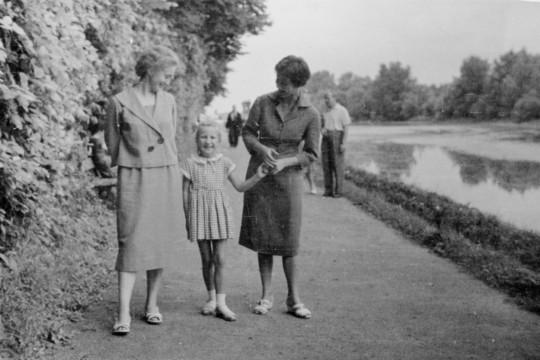 Ścieżka nad Jeziorem Wilanowskim. Po prawej stronie wysoki żywopłot. Dwie kobiety patrzą na stojącą miedzy nimi dziewczynkę. Jedna z nich trzyma ją za rękę. W tle spacerują ludzie.