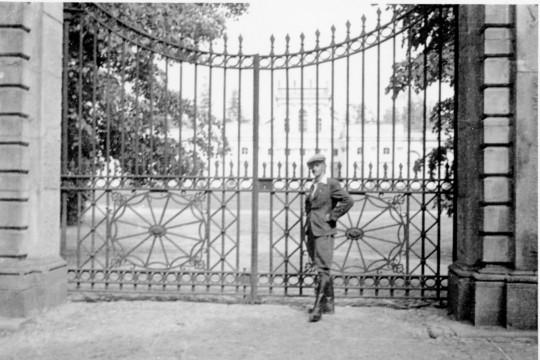 Zbliżenie na bramę. Przed nią stoi mężczyzna w garniturze, podpiera ręce na bokach, jedną nogę wysuwa do przodu.